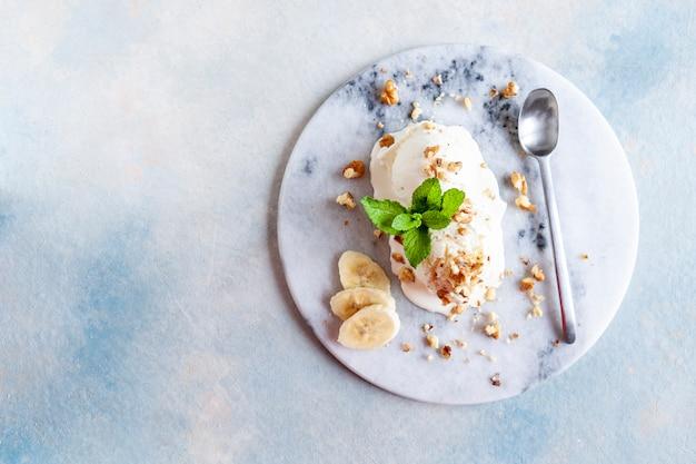Gustoso gelato cremoso fatto in casa con noci, banana e menta sul piatto di pietra