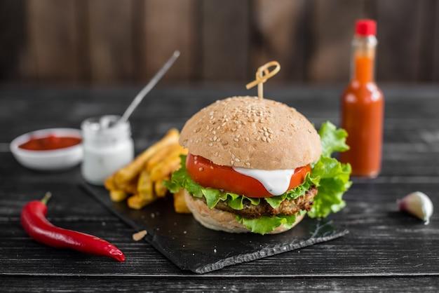 Gustoso hamburger con carne e verdure contro uno sfondo scuro. fast food. può essere usato come sfondo