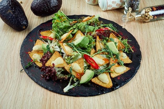 Gustoso piatto con antipasti. antipasti. chip nachos con mozzarella al forno e peperoncino su una lavagna di ardesia nera su un tavolo di legno. cucina messicana. avvicinamento