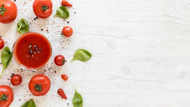 Gustoso pomodoro gustoso con spezie e spinaci sul tavolo bianco