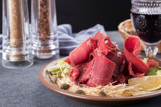 Gustoso stroganina di carne cruda surgelata, capperi e limone. carne cruda congelata affettata su un piatto. merenda fredda