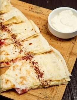 Gutab di verdure tradizionali a base di carne, qutab, gozleme su tavola di legno con sumakh, yogurt