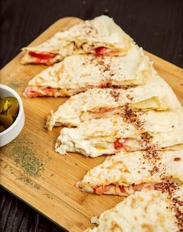 Gutab tradizionale di verdure a base di carne, qutab, gozleme su tavola di legno con sumakh, turshu.