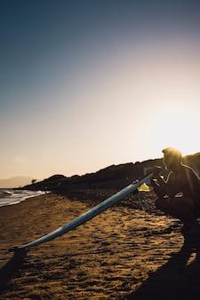 Guy con tavola da surf in spiaggia