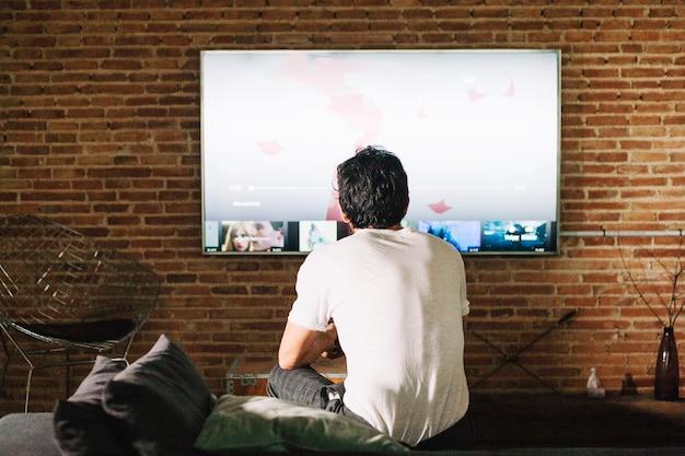 Guy dalla schiena a guardare la televisione