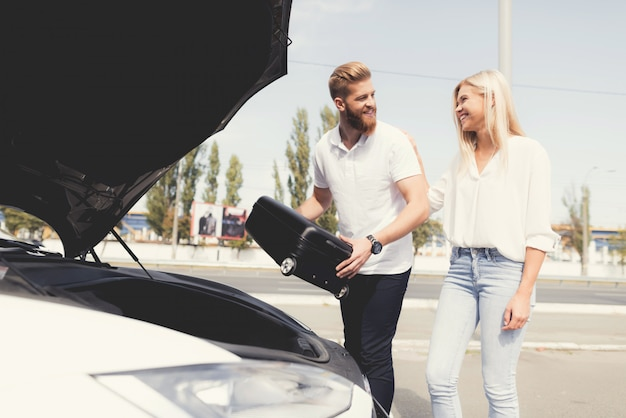 Guy e una ragazza mettono i bagagli nel bagagliaio della loro auto elettrica