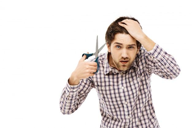 Guy guarda specchio mentre si taglia i capelli, taglio di capelli