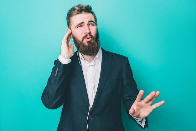 Guy in suite è in piedi e ascolta la musica al telefono