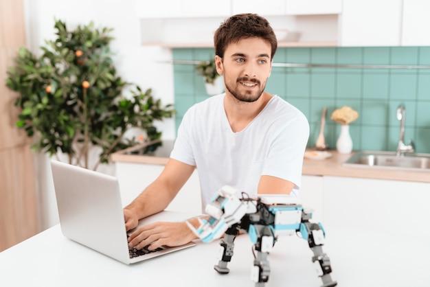 Guy lavora in un computer portatile grigio. uomo occupato che posa sorridere.