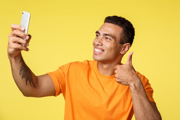 Guy registra il feedback video sul prodotto, consiglia. giovane attraente con tatuaggio, tenere smartphone, fare selfie o fare vlog, mostrare il gesto del pollice in su, sorridere compiaciuto, soddisfatto della vacanza