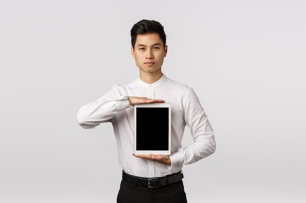 Guy sa esattamente cosa ti serve. uomo asiatico impertinente ed elegante dall'aspetto serio in abito formale, con tavoletta digitale sul petto, schermo del dispositivo, promozione dell'applicazione o collegamento aziendale