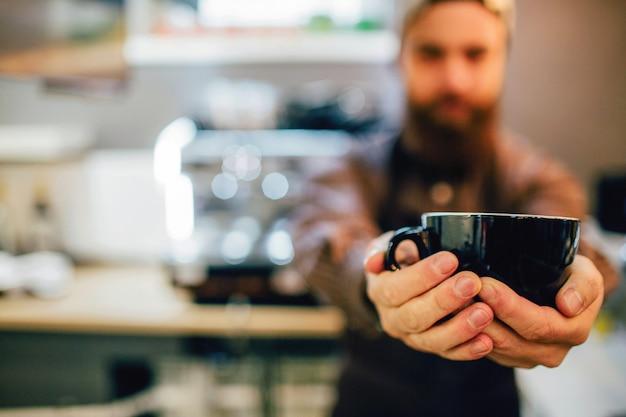 Guy tiene la tazza con entrambe le mani