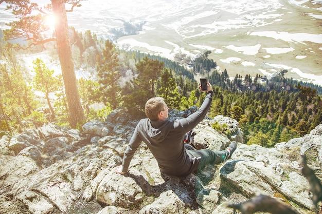 Guy traveller scatta foto di sé su uno smartphone sullo sfondo delle montagne.