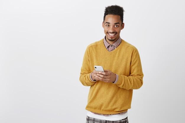 Guy vuole fare una chiamata. tiro al coperto di modello maschio afroamericano bello soddisfatto con taglio di capelli afro in maglione giallo, tenendo lo smartphone, sorridendo ampiamente mentre messaggistica con un amico