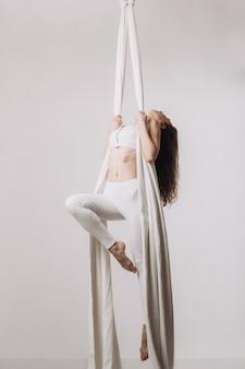 Gymnast femminile facendo acrobazie aeree di seta