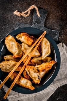 Gyoza fritti asiatici su piastra scura, servito con le bacchette e salsa di soia
