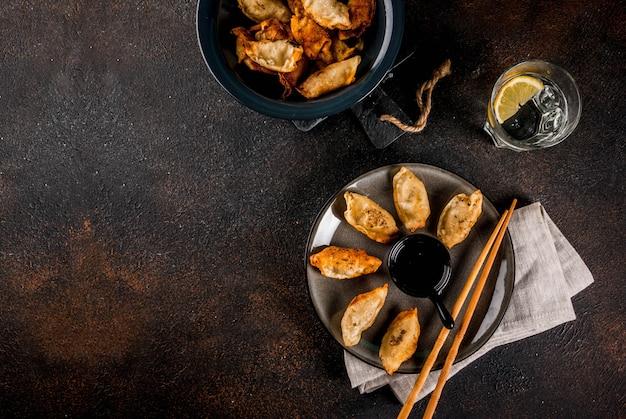 Gyoza fritti di gnocchi asiatici sul piatto scuro servito con bacchette e salsa di soia