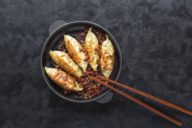 Gyoza fritti in padella, salsa di soia e bacchette su una superficie nera vista dall'alto.
