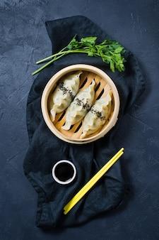 Gyoza giapponese in un tradizionale piroscafo, bacchette gialle