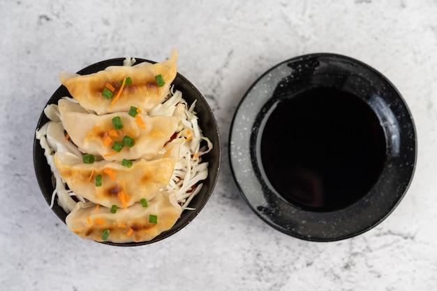 Gyoza in una tazza nera con una tazza di salsa.