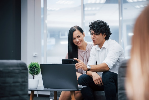 Ha una pausa. un selfie di due impiegati sorridenti in vestiti ufficiali che si siedono vicino al computer portatile d'argento sul tavolo