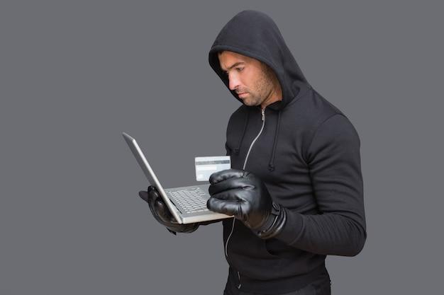 Hacker che usa il laptop per rubare l'identità