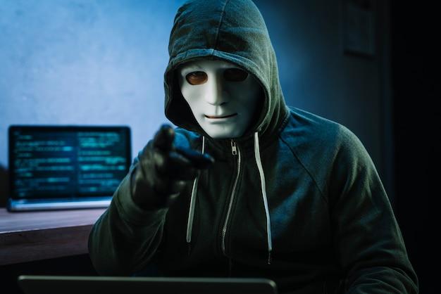 Hacker con maschera davanti al computer portatile