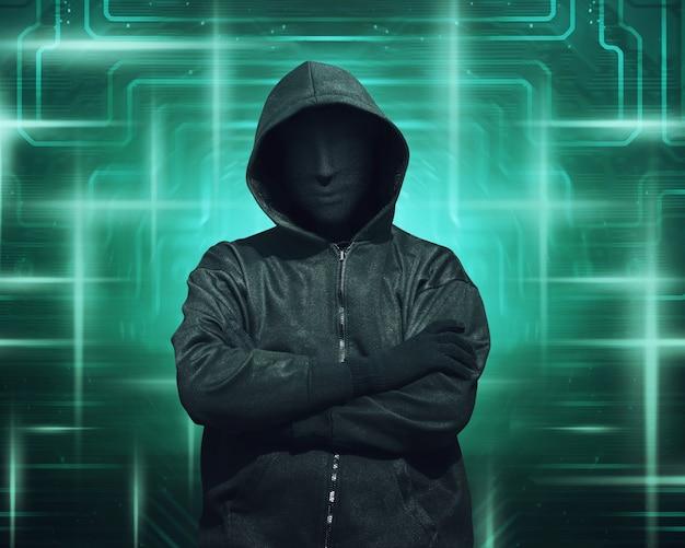 Hacker incappucciato con la mascherina in piedi