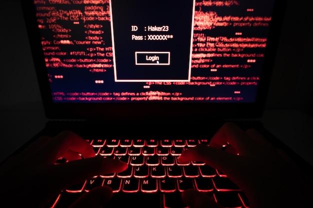 Hacker utilizzando laptop nel dark web.