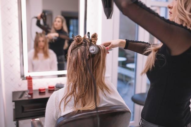 Hairstylist professionale che fissa i capelli del cliente