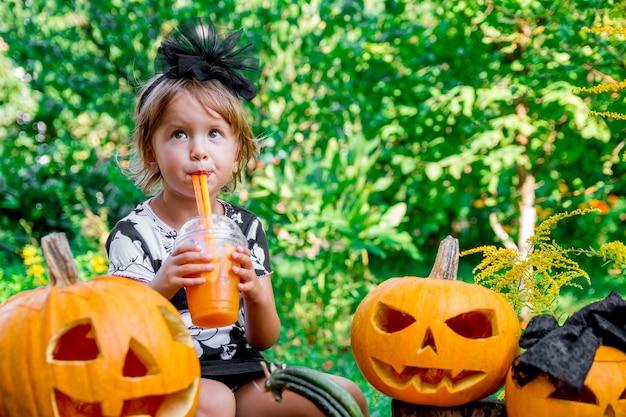 Halloween. bambino vestito di nero bere cocktail di zucca, dolcetto o scherzetto. bambina vicino alla decorazione di jack-o-lantern in legno, all'aperto.
