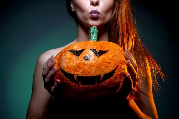 Halloween, donna in biancheria intima con zucca nelle sue mani.