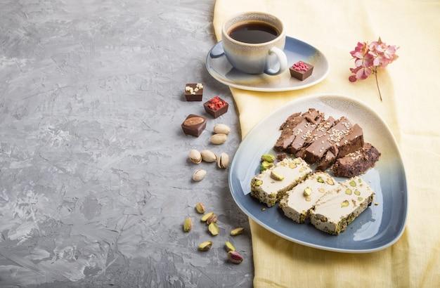 Halva tradizionale del sesamo dei dolci arabi con cioccolato e pistacchio e una tazza di caffè su un fondo concreto grigio, vista laterale, spazio della copia.