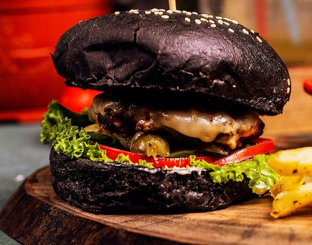 Hamburger al formaggio di manzo in padella al cioccolato nero con verdure e fast food.