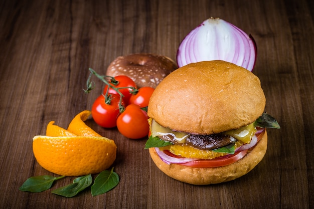 Hamburger artigianale vegetariano con formaggio, arancia, foglie di basilico, funghi shiitake e cipolla viola sul tavolo di legno