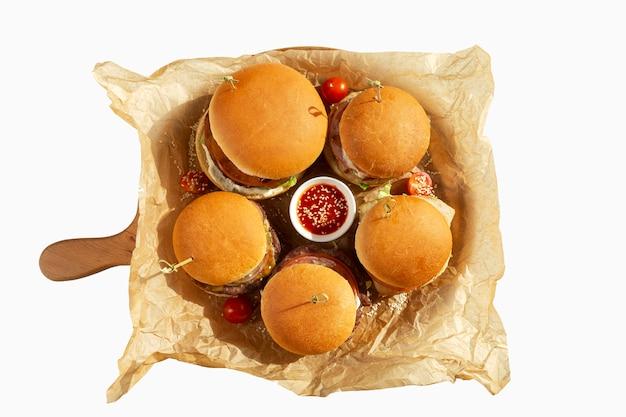 Hamburger assortito con salsa al pomodoro su un bordo di legno. vista dall'alto isolato su bianco