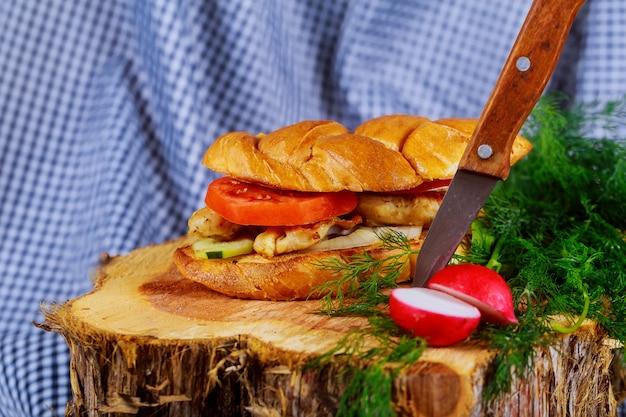Hamburger casalingo con il primo piano del bordo di legno del pollo