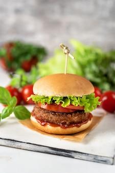 Hamburger casalingo del vegano su superficie rustica bianca