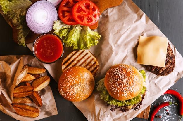 Hamburger casalingo fresco delizioso su una tavola di legno. accanto al componente per hamburger, vassoi di legno, patate fritte e peperoncino. un bicchiere di succo di pomodoro