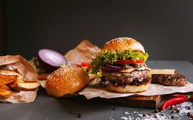 Hamburger casalingo fresco delizioso su una tavola di legno. accanto al componente per hamburger, vassoi di legno, patate fritte e peperoncino.