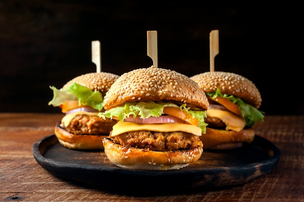 Hamburger casalingo fresco delizioso sul piatto di legno