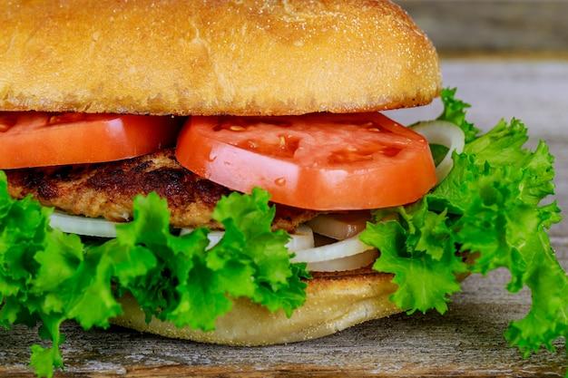 Hamburger casalingo fresco sulla piccola immagine di legno del quadrato del tagliere con il fuoco selettivo