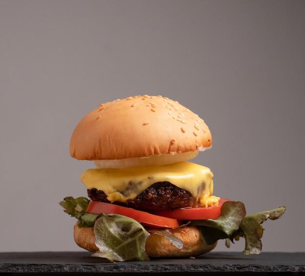 Hamburger casalingo saporito fresco con gli ortaggi freschi, lattuga, pomodoro, formaggio su un tagliere.