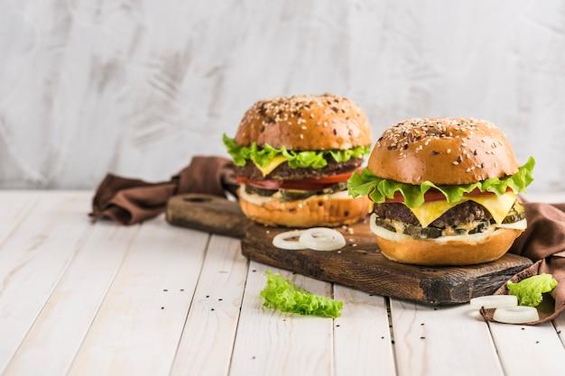 Hamburger classico con tortino di manzo, lattuga fresca, cipolle, sottaceti, formaggio cheddar e pomodori su un primo piano di tavola di legno con copyspace.