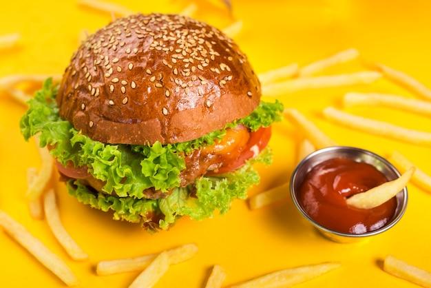 Hamburger classico del primo piano con le patate fritte e la salsa