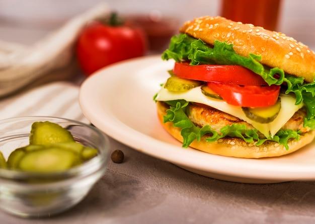 Hamburger classico saporito con il primo piano delle fette del pomodoro
