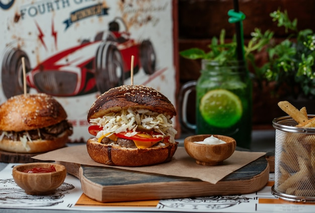 Hamburger con bistecca di manzo e insalata servita all'interno con un barattolo di mojito