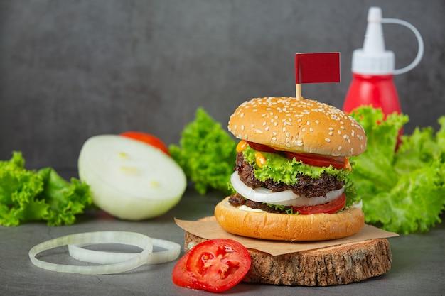 Hamburger con carne fritta, pomodori, sottaceti, lattuga e formaggio.