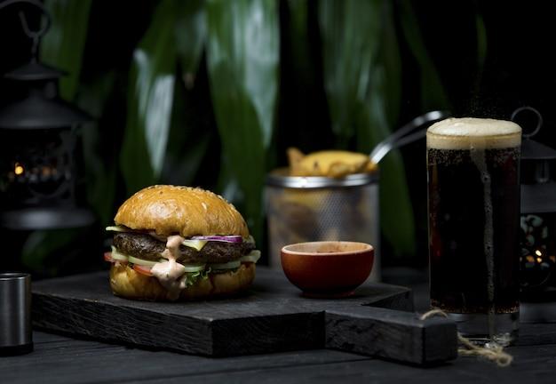 Hamburger con formaggio fondente e bistecca in uno spazio buio