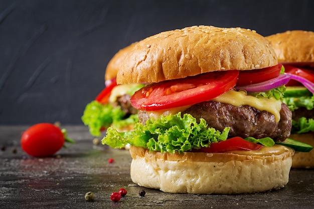 Hamburger con hamburger di carne di manzo e verdure fresche su sfondo scuro. cibo gustoso.